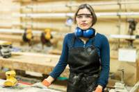 Pretty young Hispanic female carpenter wearing protective equipment in a woodshop